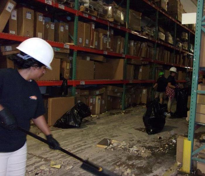 Team members in action during a warehouse cleanup.
